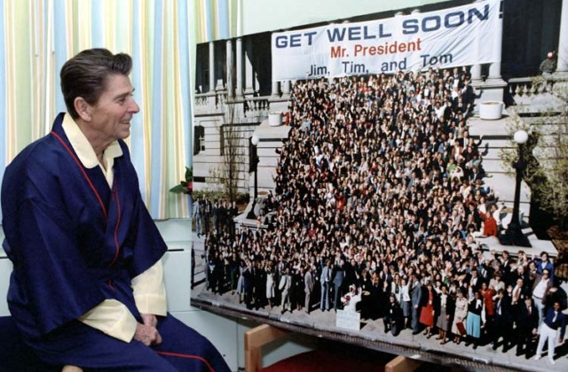"President Reagan looking at ""Get Well Soon Mr. President"" photo while at George Washington Hospital. 4/8/81. (Reagan Library)"