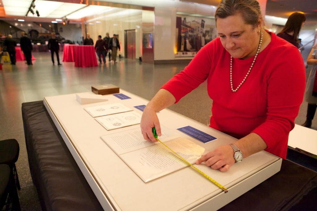 Registrar Karen Hibbitt arranges the documents for the display case.
