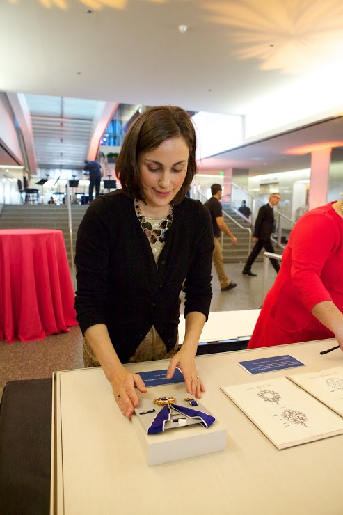 Lauren Varga adjusts a Medal of Freedom on loan from the White House.