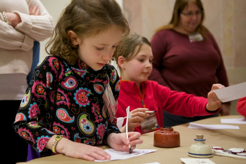 Sleepover participants get to try their hand at a variety of historical activities. Here, one young participant practices writing with a quill.