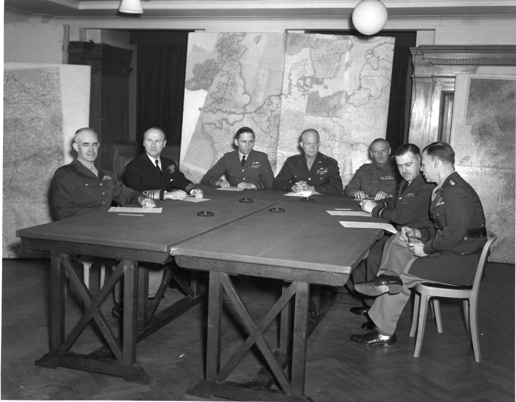 Eisenhower meets with his commanders in January 1944.  Far left is Lt. Gen. Omar Bradley and far right is Lt. Gen. Walter Bedell Smith.