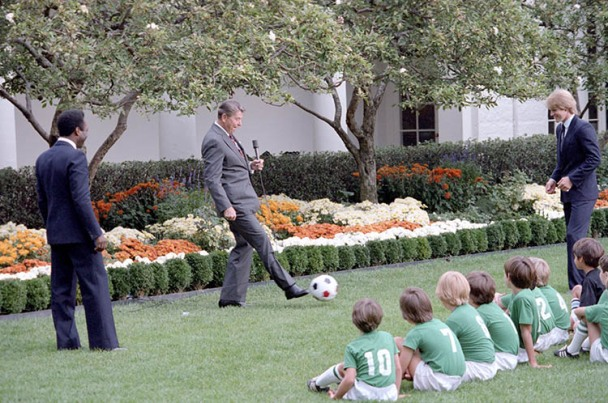 President Reagan kicking a soccer ball during a demonstration with children and Pele and Steve Moyers in the rose garden, 10/14/1982. (Ronald Reagan Presidential Library and Museum)