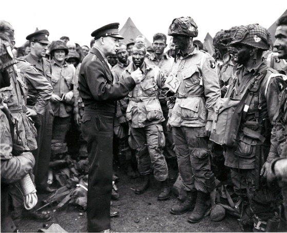 "General Dwight D. Eisenhower talks with paratroopers of the 101st Airborne Division in Newbury, England, on June 5, 1944, prior to their departure for their role in the D-day invasion, dropping behind enemy lines.  The soldier with a ""23"" tag was a fellow Kansan, Lt. Wallace C. Strobel."