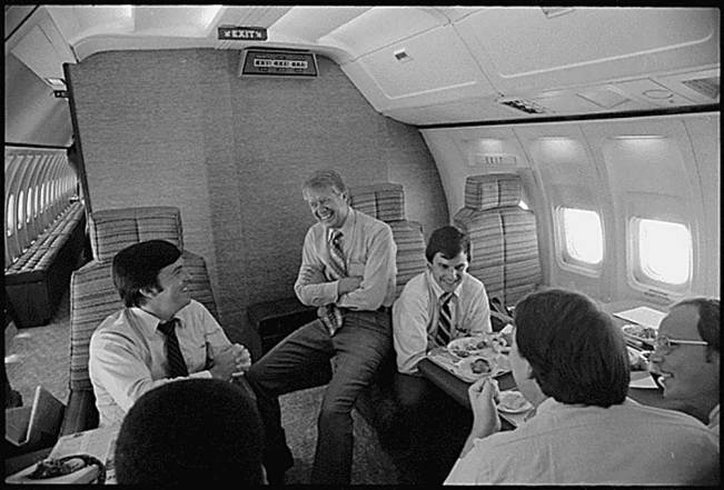 President Jimmy Carter with White House staff aboard Air Force One. 7/20/1977