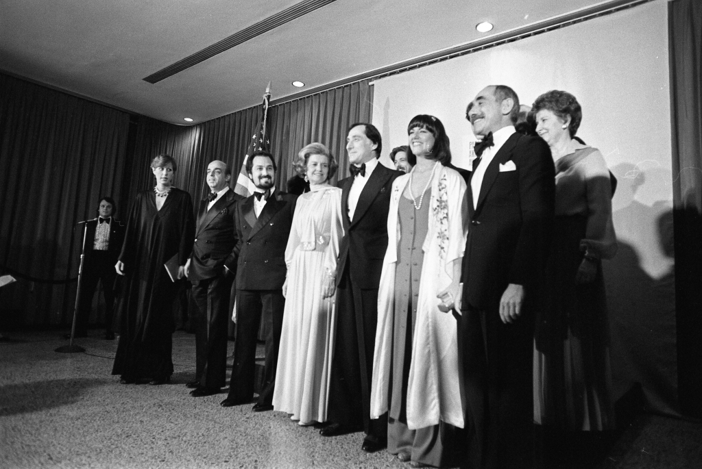 Photograph of First Lady Betty Ford with designers Donna Karan, Donald Brooks, Albert Capraro, Kasper, Kay Unger, Chester Weinberg; Liz Claiborne, Shannon Rodgers, Leo Narducci, Anthony Muto, and Calvin Klein, 03/29/1976. (National Archives Identifier 7347181)