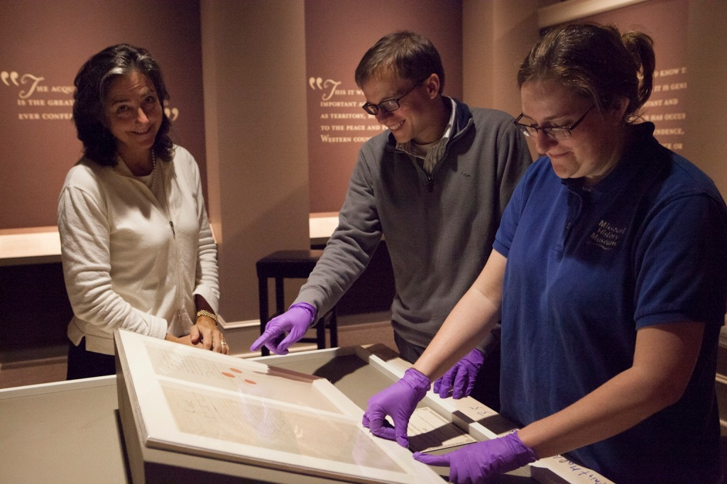 Terry Boone of the National Archives and Matt Gurley and Amanda Bailey of the Missouri History Museum prepare the Louisiana Purchase Treaty. (Missouri History Museum)