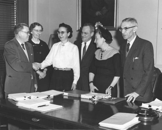 Ph.D. oral examination board for Mabel Deutrich at National Archives Building, 1960.  From left: Wayne Grover, Elizabeth Drewry, Mabel Deutrich, Sherrod East, Helen L. Chatfield, and Ernst Posner (National Archives, 64-NA-1839)