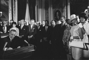 Photograph of President Lyndon Johnson signing the Voting Rights Act as Martin Luther King, Jr., and other Civil Rights Leaders in the Capitol Rotunda, Washington, DC, April 6, 1965. (National Archives Identifier 2803443).