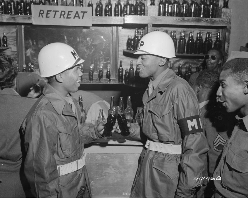 "Military Police officers toast with their Coca-Colas at a ""Retreat Club,"" July 21, 1945. (Records of the Office of the Chief Signal Officer, National Archives)"
