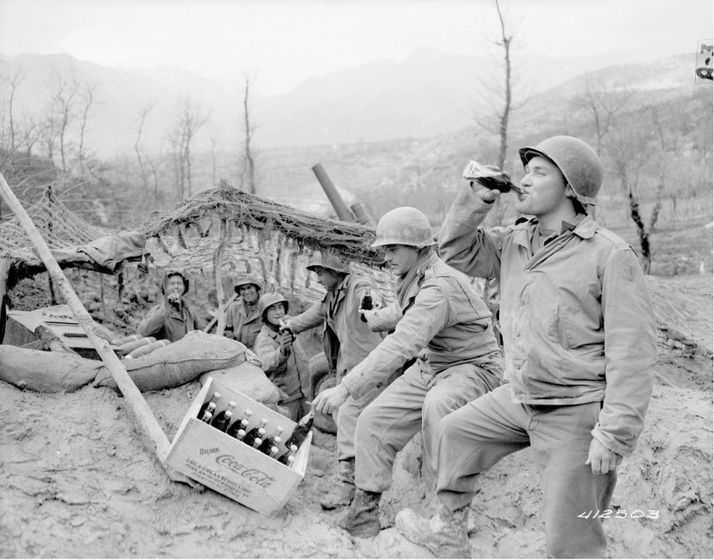 Men of the 133rd Field Artillery Battalion enjoy Cokes on the front, March 17, 1944. (Records of the Office of the Chief Signal Officer, National Archives)