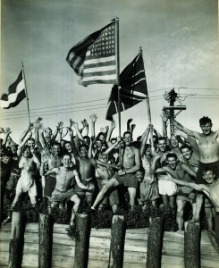Gaunt Allied prisoners of war, waving flags of the United States, Great Britain, and Holland at Aomori camp near Yokohama, Japan, cheer rescuers from the U.S. Navy on August 29, 1945. (80-G-490444; National Archives Identifier 520992)