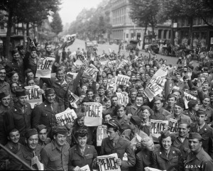 "American servicemen and women gather in front of ""Rainbow Corner"" Red Cross club in Paris to celebrate the conditional surrender of the Japanese on August 15, 1945. (111-SC-210241)"