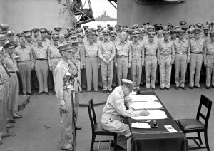 Gen. Douglas MacArthur signs as Supreme Allied Commander during formal surrender ceremonies on the USS Missouri in Tokyo Bay. Behind him are American Lt. Gen. Jonathan Wainright and British Lt. Gen. Arthur Percival, both of whom were held as prisoners of war by the Japanese. (80-G-348366; National Archives Identifier 520694)