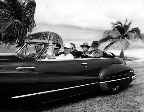 President Harry S. Truman stops the motorcade at a scenic spot on the highway to Key West after going to Boca Chica to meet additional guests who arrived late. In the front seat, left to right: unidentified, Admiral William Leahy, President Truman. Back seat, left to right: Harry Vaughan, Judge John Caskie Collet, and John Steelman. 11/20/46.